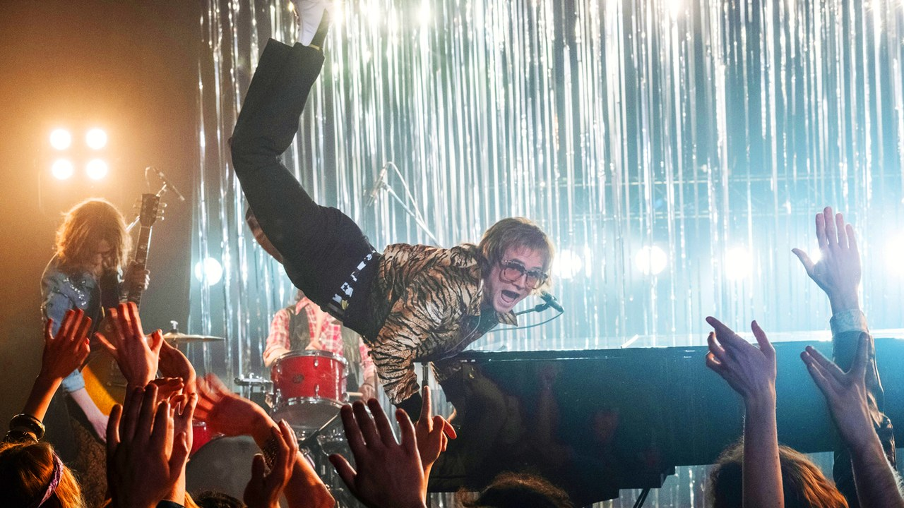 Taron Egerton in mid-air as he plays the piano in the film Rocketman (2019).