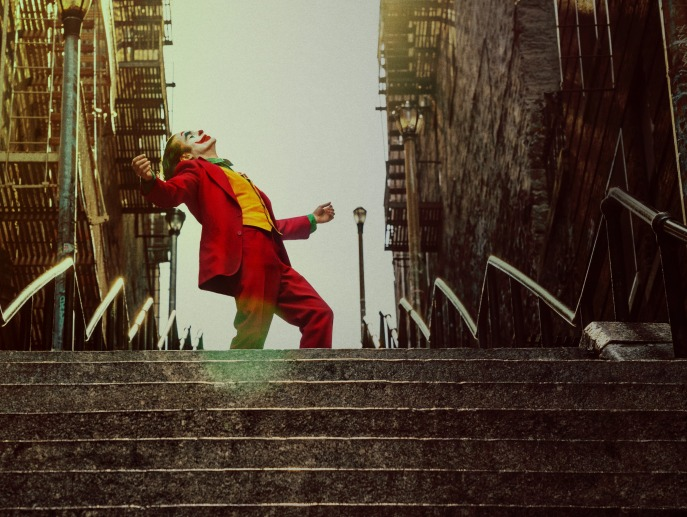 Image of Joaquin Phoenix as Joker atop a flight of stairs